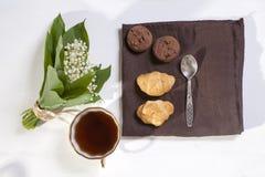 Xícara de café branca, um ramalhete dos lírios do vale, um bloco de notas para notas e uns pires com as duas cookies da brownie C Imagem de Stock