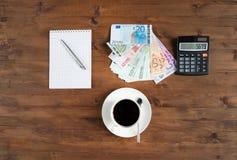 Xícara de café, calculadora, bloco de notas e euro- dinheiro Fotografia de Stock Royalty Free