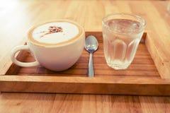 Xícara de café com água na tabela Foto de Stock Royalty Free