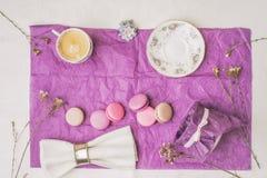 Xícara de café com bolinhos de amêndoa e decoração no papel roxo Foto de Stock