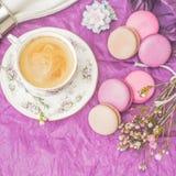 Xícara de café com bolinhos de amêndoa e decoração no quadrado de papel roxo Fotografia de Stock Royalty Free
