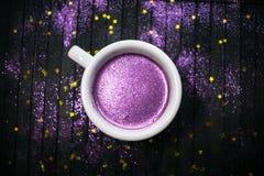 Xícara de café com brilho roxo no fundo escuro com dourado fotos de stock royalty free