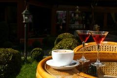 Xícara de café com creme e dois vidros com licor Fotografia de Stock Royalty Free