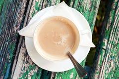 A xícara de café com creme está no banco de madeira velho Foto de Stock