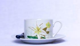 Xícara de café com detalhes florais em uma placa foto de stock