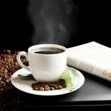 Xícara de café com embaçamento com portátil, jornal, folha do café no café da manhã Fotos de Stock