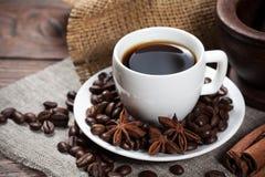 Xícara de café com feijões e especiarias Fotografia de Stock Royalty Free