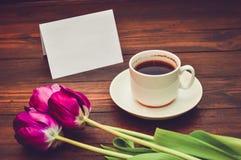 Xícara de café com flores e um cartão para inscrição em um fundo de madeira fotos de stock