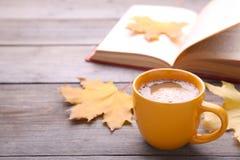 Xícara de café com folha e livro do outono no fundo cinzento imagem de stock