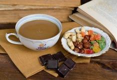 Xícara de café com frutos e chocolate secos no guardanapo Foto de Stock