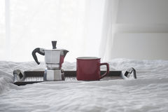 Xícara de café com kattle em uma bandeja de madeira na cama branca Imagens de Stock Royalty Free