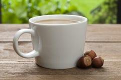 Xícara de café com leite e avelã Fotografia de Stock Royalty Free
