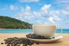 Xícara de café com o feijão de café no fundo da praia Foto de Stock