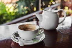 Xícara de café com o potenciômetro quente do chá em de madeira Imagens de Stock