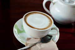 Xícara de café com o potenciômetro quente do chá em de madeira dentro sobre o tom escuro Imagens de Stock