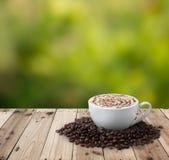 Xícara de café com os feijões de café na tabela Fotografia de Stock