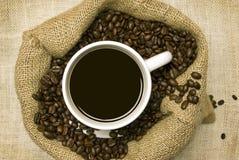 Xícara de café com os feijões de café no saco Fotografia de Stock Royalty Free