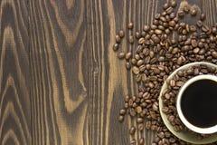 Xícara de café com os feijões que estão em uma tabela de madeira Foto de Stock Royalty Free