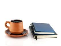Xícara de café com pires e dois livros do diário Fotos de Stock Royalty Free