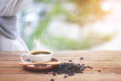 Xícara de café com ` s do feixe do café e jornais, perto da janela Fotografia de Stock