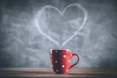 Xícara de café com um vapor dado forma coração Foto de Stock