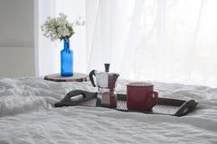 Xícara de café com um vaso azul em uma bandeja de madeira na cama branca Foto de Stock