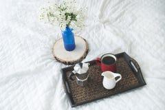 Xícara de café com um vaso azul em uma bandeja de madeira na cama branca Imagem de Stock Royalty Free