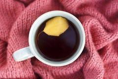 Xícara de café com uma folha do outono em um close-up feito malha do tapete, vista superior foto de stock