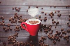 Xícara de café com vapor e feijões da forma do coração Imagem de Stock