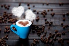 Xícara de café com vapor e feijões da forma do coração Imagem de Stock Royalty Free