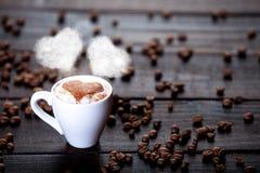 Xícara de café com vapor e feijões da forma do coração Imagens de Stock Royalty Free