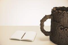 A xícara de café compôs das letras em uma tabela de madeira com o diário Fotografia de Stock