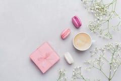 Xícara de café da manhã, macaron do bolo, presente ou caixa e flor atuais na tabela clara de cima de Configuração bonita do plano Fotografia de Stock Royalty Free