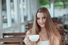 Xícara de café da terra arrendada da mulher que olha o sorriso da câmera imagens de stock