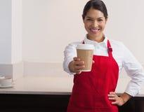 Xícara de café de oferecimento do barista consideravelmente novo para ir sorrir na câmera fotografia de stock