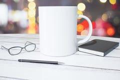 Xícara de café, diário, vidros e pena brancos em uma tabela de madeira fotografia de stock royalty free
