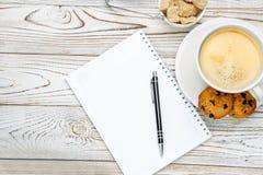 Xícara de café e almofada de nota na tabela de madeira clara Imagens de Stock