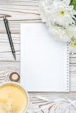 Xícara de café e almofada de nota na tabela de madeira clara Fotografia de Stock