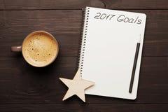 Xícara de café e caderno com objetivos para 2017 na tabela de madeira de cima de Planeamento e motivação para o conceito do ano n Foto de Stock
