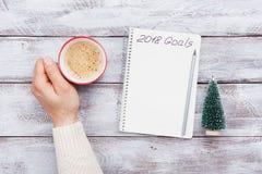Xícara de café e caderno masculinos da posse da mão com objetivos para 2018 Planeamento e motivação para o conceito do ano novo V Foto de Stock Royalty Free