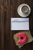 Xícara de café e caderno mordidos da filhós Fotografia de Stock