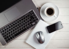 Xícara de café e caderno, portátil, rato do computador, telefone em um t Fotos de Stock Royalty Free
