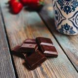 Xícara de café e chocolate em uma tabela de madeira imagem de stock