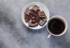 Xícara de café e chocolate escuro na placa branca no fundo cinzento, vista superior fotos de stock royalty free