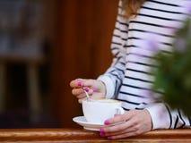 Xícara de café e colher na mulher das mãos imagens de stock