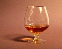 Xícara de café e conhaque brancos em uns vidros, confeitos no fundo vermelho Imagem de Stock Royalty Free