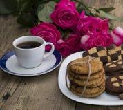 Xícara de café e cookies em uma placa com um ramalhete das rosas Foto de Stock