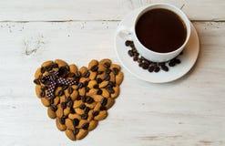 Xícara de café e coração com amêndoas em um fundo branco Fotografia de Stock
