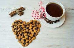 Xícara de café e coração com amêndoas em um fundo branco Fotografia de Stock Royalty Free