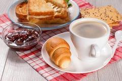 Xícara de café e croissant nos pires, bacia de vidro com strawberr Fotos de Stock Royalty Free